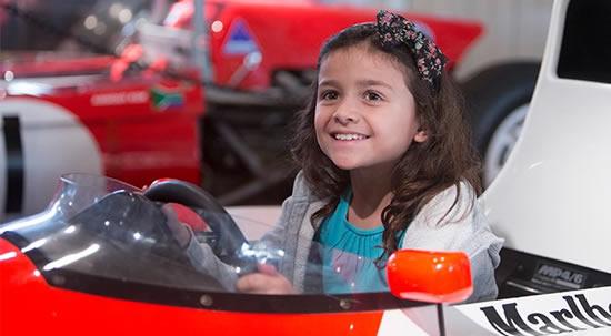 Girl sitting in F1 Racing Car at Brooklands Museum Weybridge Surrey